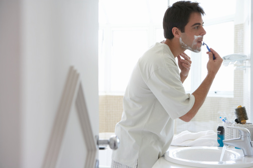 Man shaving face in bathroom mirror, side view 200476137-001