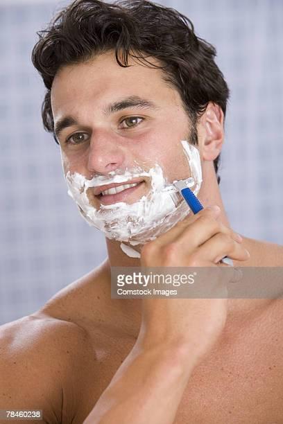 Man shaving face with razor