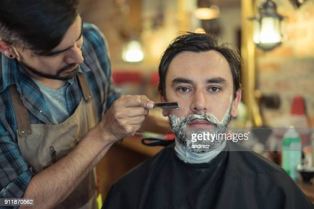 Man shaving his beard at a retro barber shop