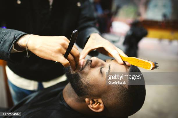 man shaving in barber shop - barber stock pictures, royalty-free photos & images