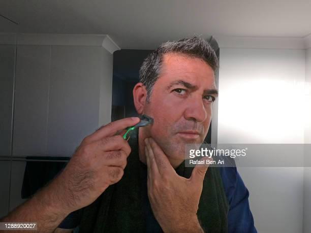 man shaving looking at mirror - rafael ben ari - fotografias e filmes do acervo