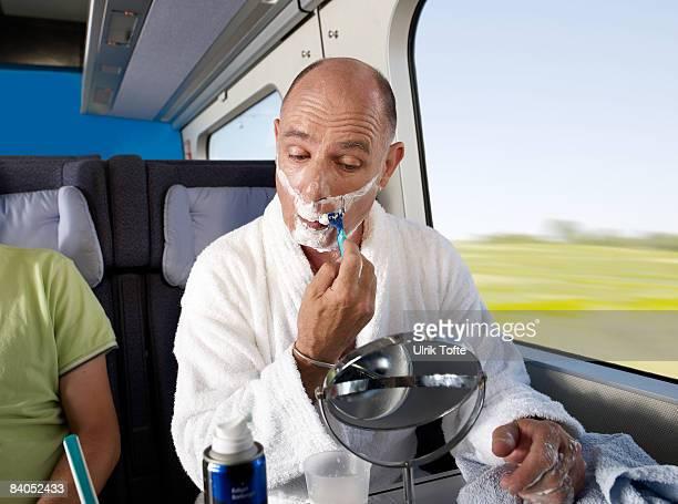Man shaving on train