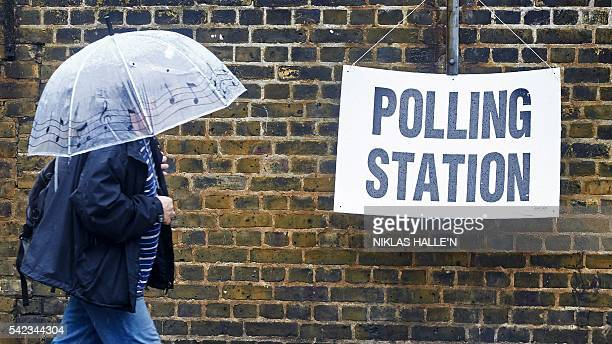 TOPSHOT A man shelters from the rain as he arrives at a polling station in London on June 23 as Britain holds a referendum on wether to stay in or...