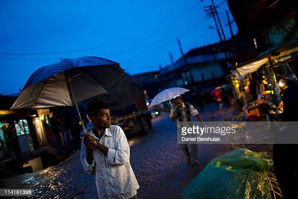 A man shelters from the rain as he looks at shop fronts on April 14 2011 in Lad Rymbai in the district of Jaintia Hills India TThe Jaintia hills...