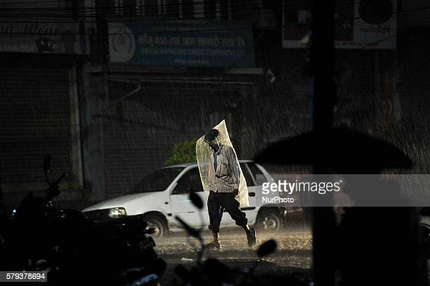 A man shelters under a temporary plastic made raincoat as going towards their home during sudden heavy rainfall on July 23 2016