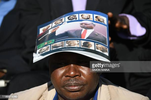 A man shields himself from the sun using a funeral programme booklet of late former Kenya President Daniel Arap Moi during the state memorial service...