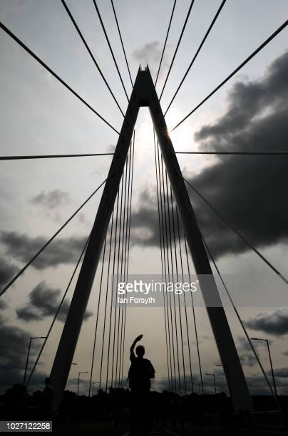 A man shields his eyes from the sun as he looks up at the central pylon of the new Northern Spire bridge spanning the River Wear as it opens for a...