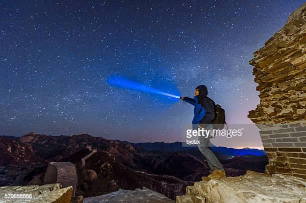 Man Shining a flashlight on The great wall at night