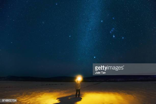 Man shining a light under the Milky Way.