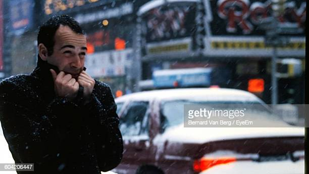 man shivering during snowfall in city - shaking stock pictures, royalty-free photos & images
