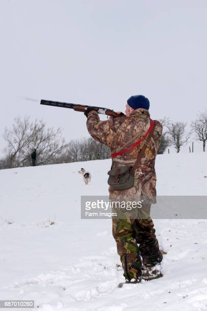 Man shooting a 12 bore shotgun on a Pheasant shoot in snowy conditions