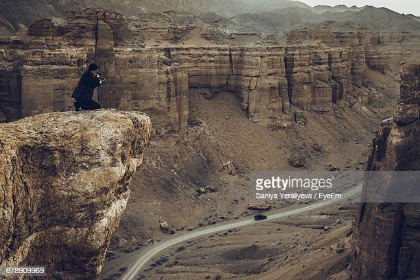 Man Shooting At A Car From A Cliff