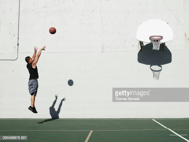 man shooting jump shot on outdoor basketball court, side view - shooting baskets stock photos and pictures