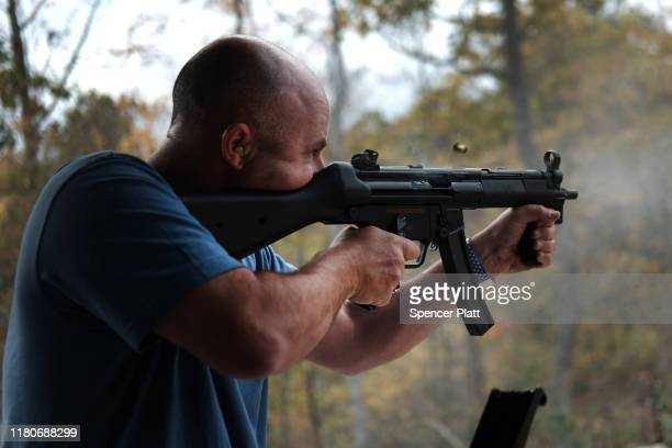 """A man shoots an automatic weapon at a shooting range during the """"Rod of Iron Freedom Festival"""" on October 12 2019 in Greeley Pennsylvania The twoday..."""