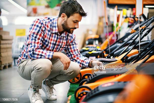 man shopping at a hardware store. - gardening equipment stock pictures, royalty-free photos & images