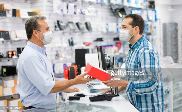 man shopping at a tech store during the pandemic and wearing facemask - biosecurity stock pictures, royalty-free photos & images