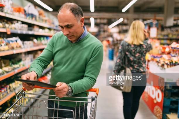 Homme du shopping au supermarché et à l'aide de tablette numérique