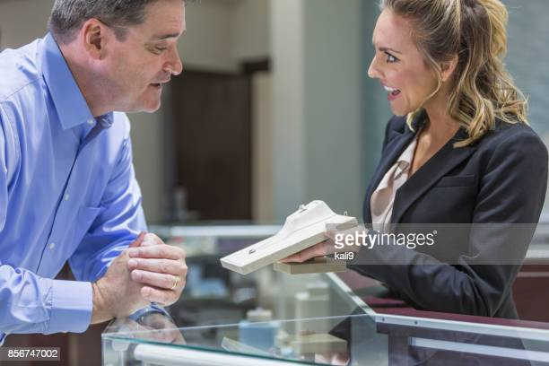 man shopping for jewelry, with saleswoman - jewellery products stock photos and pictures