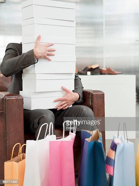 man shopping holding pile of cartons - groupe moyen d'objets photos et images de collection