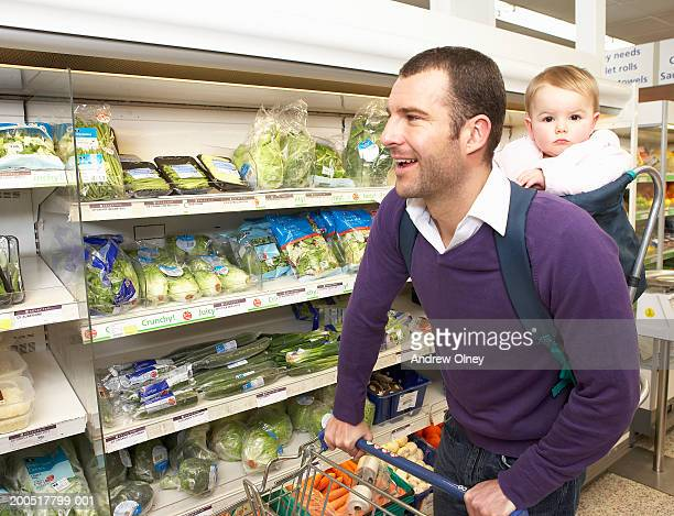 Man shopping in supermarket, carrying baby girl (9-11 months) on back