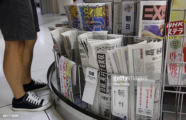 A man shops at a kiosk as newspapers including the Nikkei center are displayed for sale in Tokyo Japan on Friday July 24 2015 After almost six...