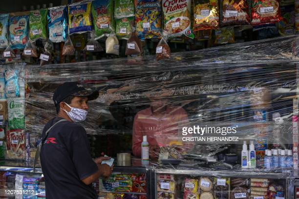 Man shops at a store covered with plastic as a precautionary measure against the spread of the new coronavirus, COVID-19, in Caracas, on March 17,...
