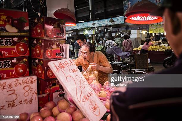 Man shops for apples at a fresh produce market in Shanghai, China, on Sunday, July 3, 2016. The yuan headed for a fifth weekly decline, the longest...