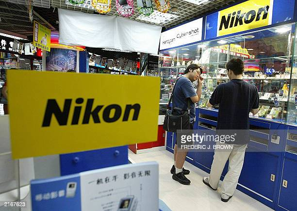 Man shops for Japanese-brand Nikon digital cameras, 09 July 2003, at a tech-mall in Beijing. China's import volume is expected to jump between 12 and...