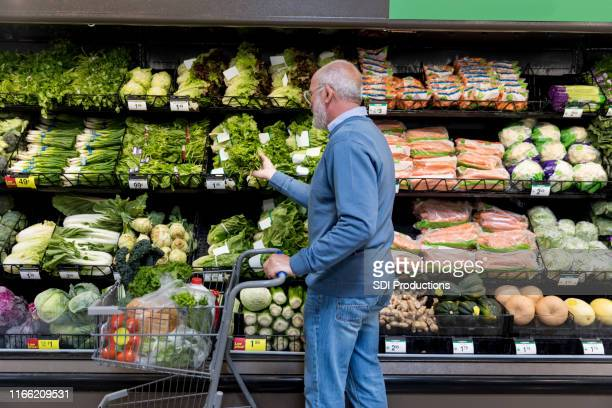 man shops for leafy greens in grocery store - produce aisle stock pictures, royalty-free photos & images