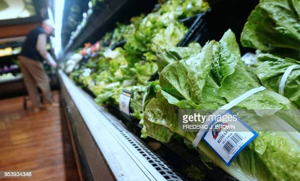 A man shops for vegetables beside Romaine lettuce stocked and for sale at a supermarket in Los Angeles California on May 2 where the first death from...
