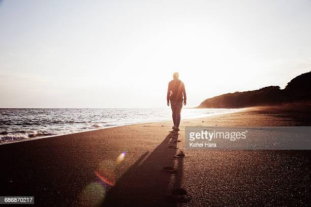 man shouldering a backpack walking in the beach - hombre de espaldas playa fotografías e imágenes de stock