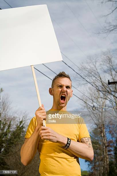 Man shouting and holding a blank placard
