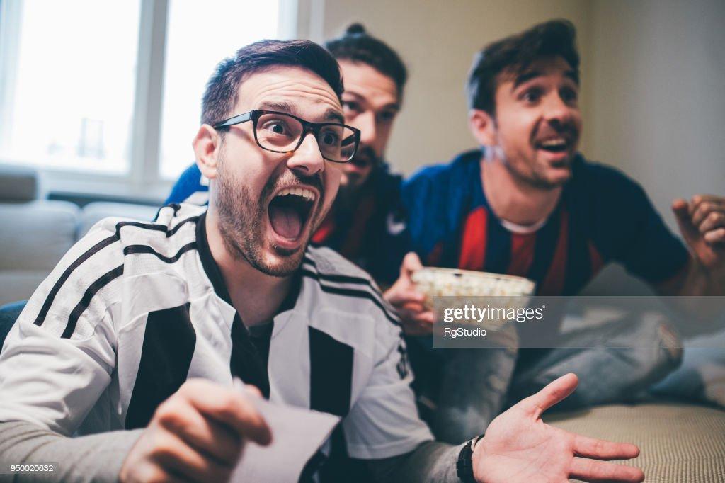 Uomo che grida e guarda la partita di calcio con gli amici con la scivolata delle scommesse in mano : Foto stock