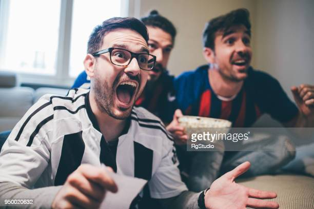 Man shouting and watching soccer game with friends with betting slip in his hand