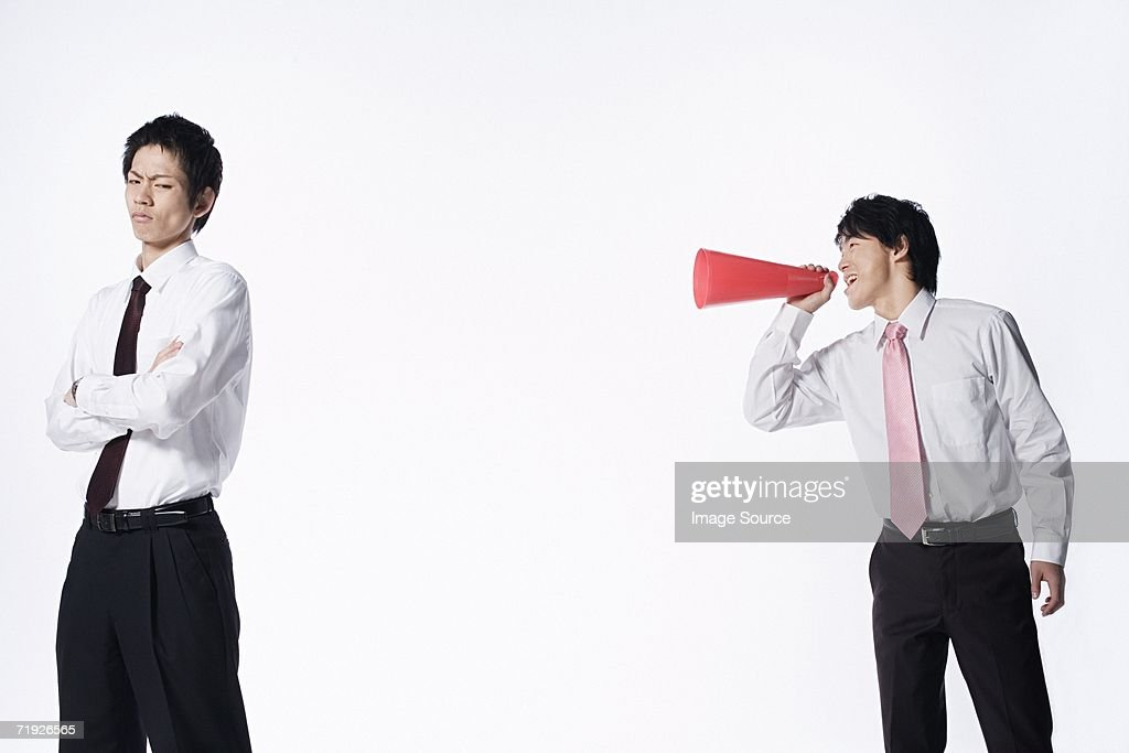 Man shouting at colleague with megaphone : Stock Photo