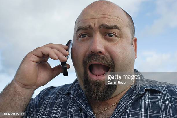 Man shouting, using mobile phone, close-up