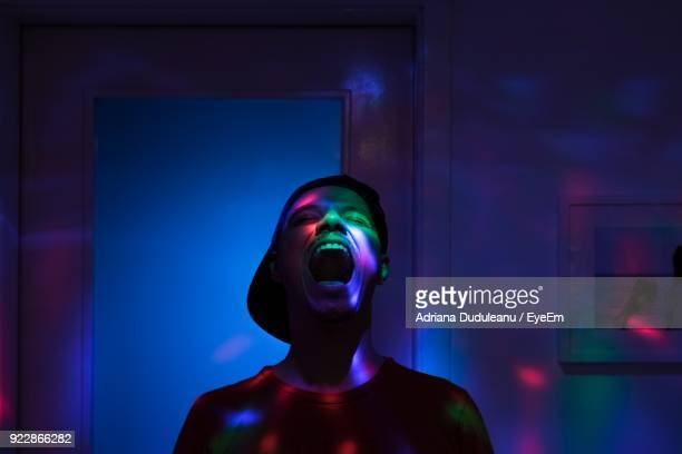 man shouting while standing in illuminated room - ディスコ照明 ストックフォトと画像