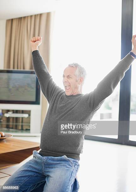 Man shouting with excitement in living room