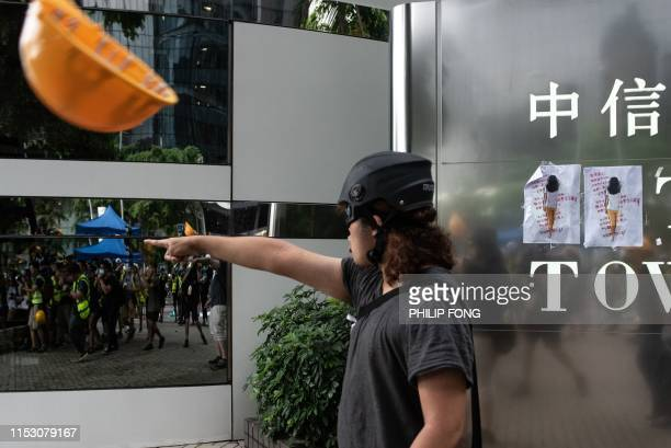 A man shouts as a helmet is thrown by protesters outside the government headquarters after the annual flag raising ceremony to mark the 22nd...
