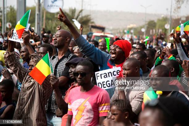 Man shouts as he holds a sign that reads, 'France get out' during a protest against French and UN forces based in Mali organized by Malian...