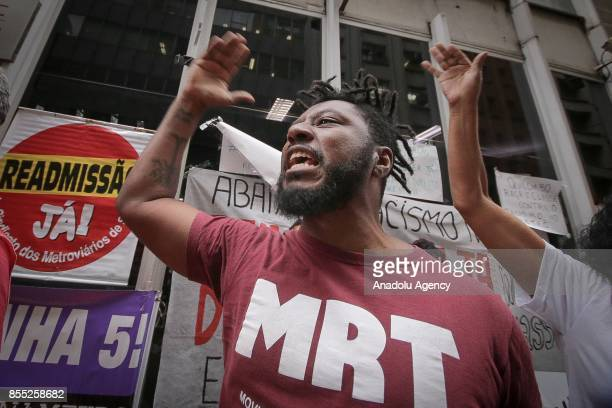 A man shouts slogans during a demonstration against employee layoffs and the expansion of the privatization of subway lines in front of the subway...