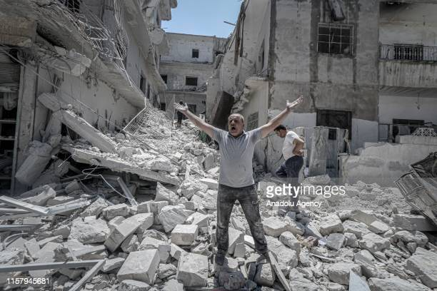 Man shouts with open hands over the debris of his damaged house after airstrikes of Assad Regime and Russia over Arihah district within the...
