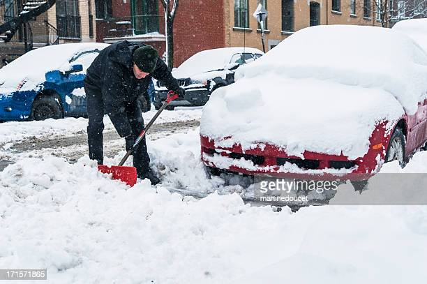 Man shoveling around his car on a snowing day.