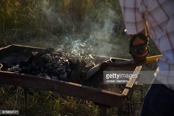 A man shoveling coals in a fire pit
