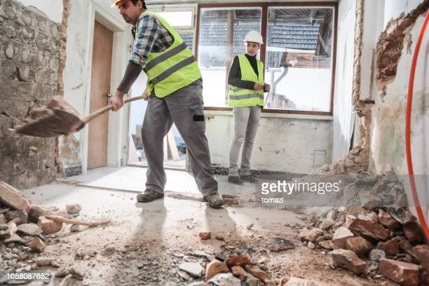 man shoveling gravel on a construction site - rubble stock pictures, royalty-free photos & images