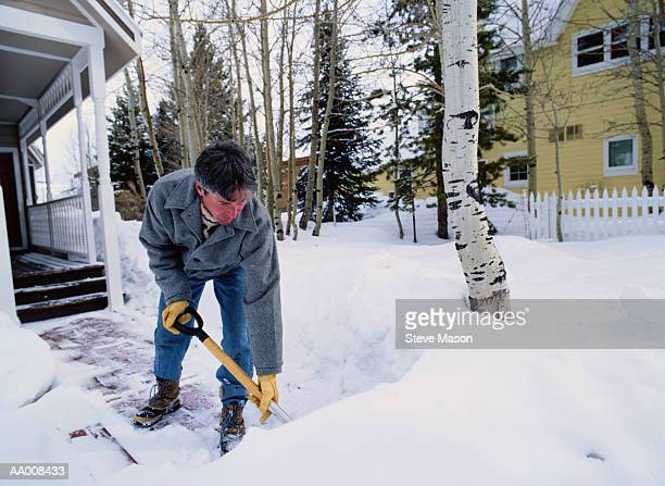 man shoveling snow from the front walkway - snow shovel stock photos and pictures