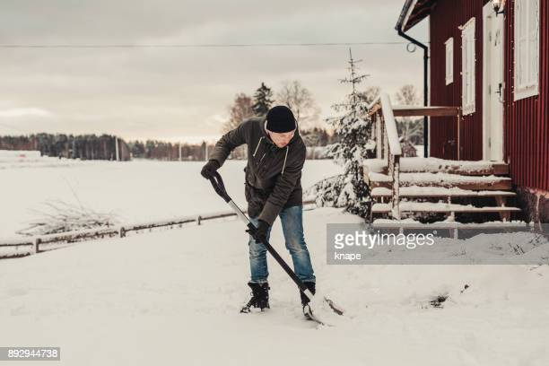 man shoveling snow outdoors - snow shovel stock photos and pictures