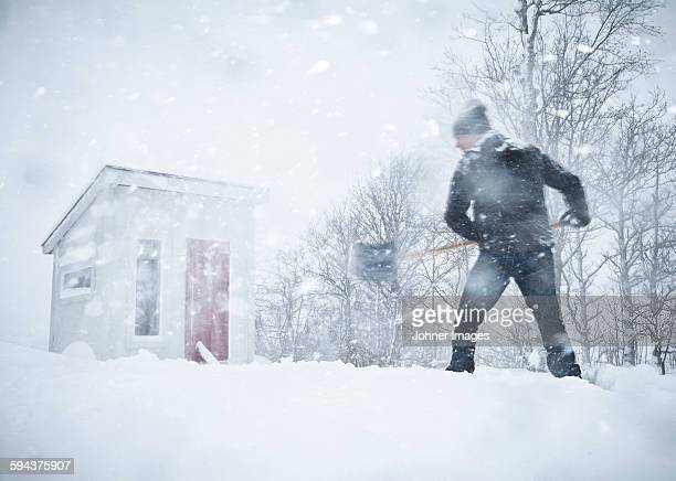 man shoveling snow - snow shovel stock photos and pictures