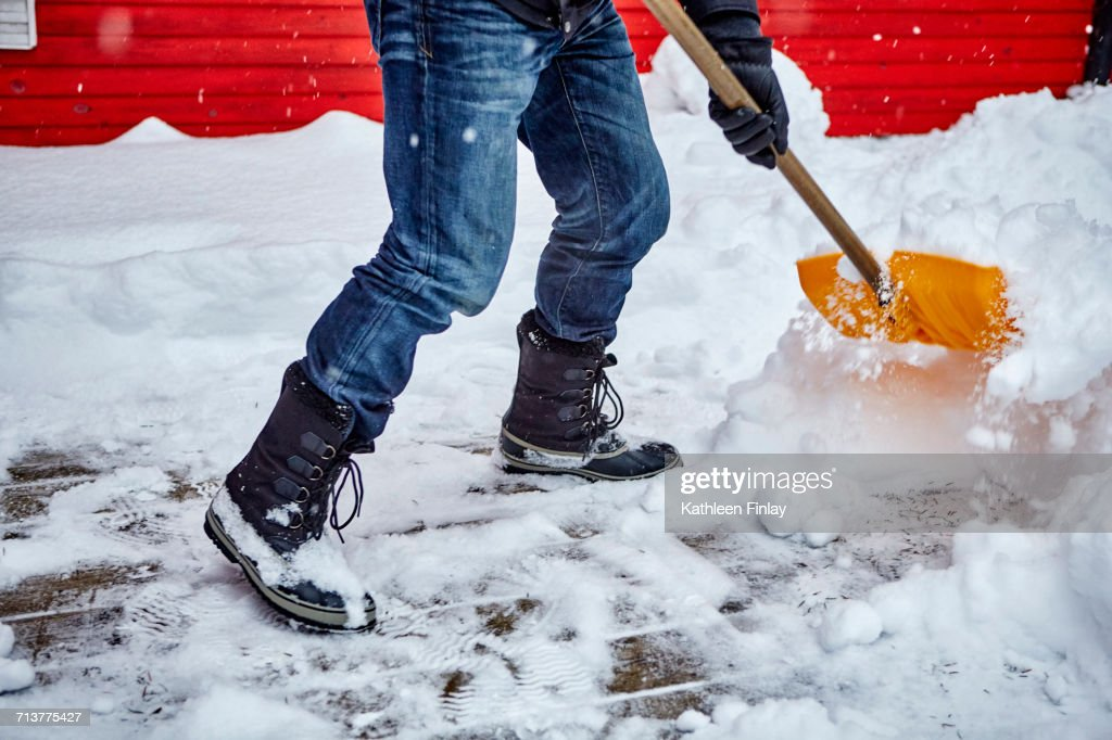 Man shovelling snow from pathway, low section : Stock Photo