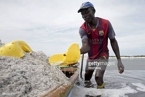 Man shovels scoops of salt collected from the bed of Lake Retba into a boat during the harvest near Dakar, Senegal, on Wednesday, July 27, 2016. The...
